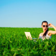 Happy girl in a green field with a laptop. summer — Stock Photo #25062499