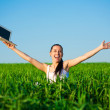 Photo: Happy freelancer girl in green field with laptop. summer