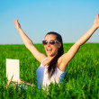 Foto Stock: Happy freelancer girl in green field with outstretched arms