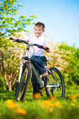 Kid in a green park on a bike — Stock Photo