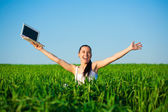 Happy freelancer girl in a green field with a laptop. summer — Стоковое фото