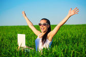 Happy freelancer girl in a green field with outstretched arms — Stok fotoğraf