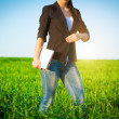 Businesswoman in a green field with a laptop. consept — Stockfoto