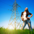 Pretty businesswoman in a field with a laptop. power lines — Stockfoto