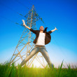 Jumping businesswoman in a green field with a laptop. power lines — Stok fotoğraf