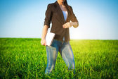 Businesswoman in a green field with a laptop. consept — Stock Photo
