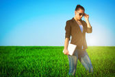 Sexy businesswoman in a green field with a laptop. idea — Stock Photo