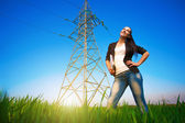 Pretty businesswoman in a field with a laptop. power lines — Stock Photo