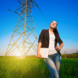 Cute woman in a green field with a laptop. power lines — Stok fotoğraf