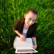 Happy girl in a green field with a laptop. summer — Stockfoto