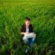 Happy girl in a green field with a laptop. summer — Stock Photo