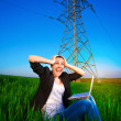 Businesswoman in a green field with a laptop. power lines — Stock fotografie