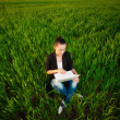 Puzzled woman in a green field with a laptop. summer — Stock fotografie