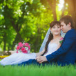 Happy newlyweds are sitting on the green grass — Stock Photo #26897021