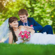Bride and groom are lying on the green grass — Stock Photo