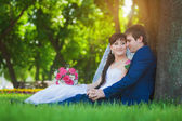 Happy newlyweds are sitting on the green grass — Stock Photo