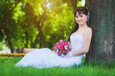 Beautiful bride in white dress sitting under a tree — Stock fotografie