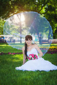 Beautiful bride with bridal veil is sitting on the green grass — Stock Photo