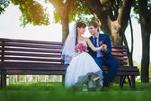 Happy bride and groom are sitting on the bench — Stock Photo