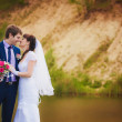 Newlyweds are hugging near the lake — Stock Photo