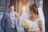 Bride and groom against a blue modern building — Stock Photo