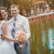Happy bride and groom in the park — Stock Photo