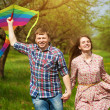 Постер, плакат: Happy couple are fling a kite on a spring meadow
