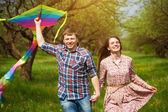 Happy couple are fling a kite on a spring meadow — Stock Photo