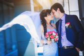 Happy newlyweds against a blue modern building background — Stock Photo
