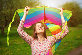 Happy woman is fling a kite on a spring meadow — Stock Photo