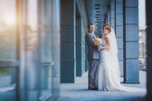 Newlyweds are hugging against a blue modern building — Stock Photo