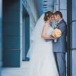 Happy newlyweds are hugging against a modern building — Foto Stock