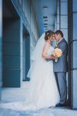 Happy newlyweds are hugging against a modern building — Stock Photo