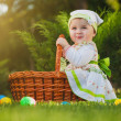 Cute baby with basket in the green park — Stock Photo #30624153
