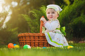 Cute baby with basket in the green park — Stock Photo