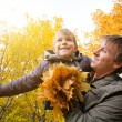 Dad and son are playing in a yellow autumn park — Stock Photo