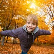 Cheerful kid on a background of sky and autumn trees — Stock Photo