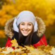 Pretty woman is lying in a yellow autumn leaves — Stock Photo