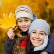 Happy Mom and son are playing in a yellow autumn — Stock Photo