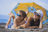 Happy smiling mom and son are sunbathing on a beach — Stock Photo