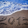 2013 inscription on a beach is washing off by a wave — Stock Photo