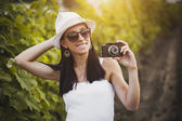 Photographer girl in the rays of the evening sun on the vineyard — Stock Photo