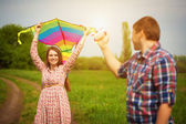 Loving couple are fling a kite on a spring meadow — Stock Photo