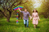 Happy couple are fling kite on a spring meadow — Stock Photo