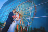 Happy newlyweds near the blue glass building — Stock Photo