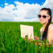 Woman in a green field with a laptop. summer — Stock Photo