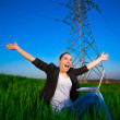 Stock Photo: Cute woman in a green field with a laptop. power lines