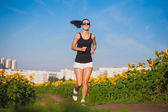 Athlete on morning jog in the sunflower's field — Stock Photo