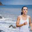 Athlete girl on morning jog on the beach — Stock Photo