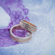 Stock Photo: Beautiful golden rings on blue wedding dress